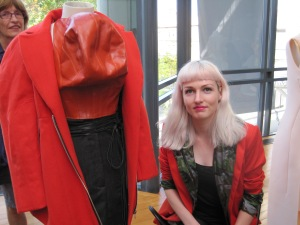 Emma with her garments: wool coat, leather top and worsted skirt. She also wears her own-design jacket. We love orange!