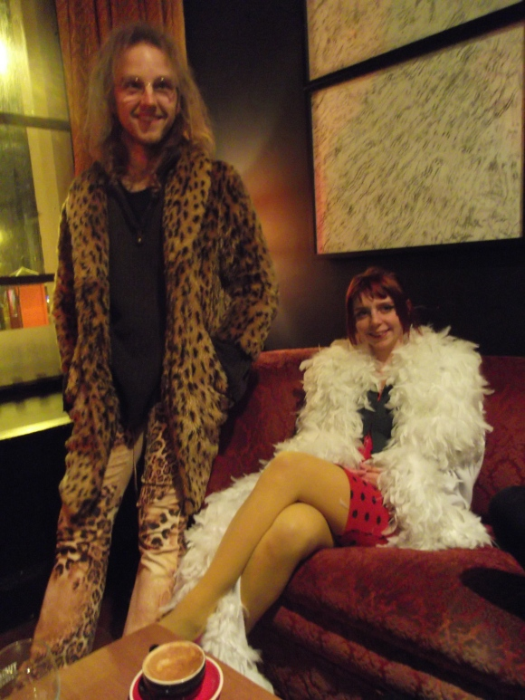 Michael Morris (Artistic Director of Operation Underground) wears coat and pants from SaveMart. Rachael dresses as a Bird of Paradise.