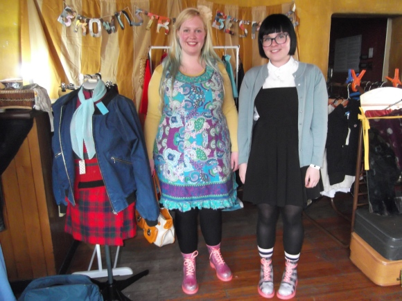 Zara and Alice. Zara wears op shop. Alice wears shirt from Oamaru, dress from Wildpair and cardigan from Butterflies Hospice Shop.