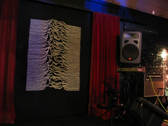 Queens stage with Joy Division's 'Unknown Pleasures' cover art based on the image of radio waves emitted by pulsar CP 1919.