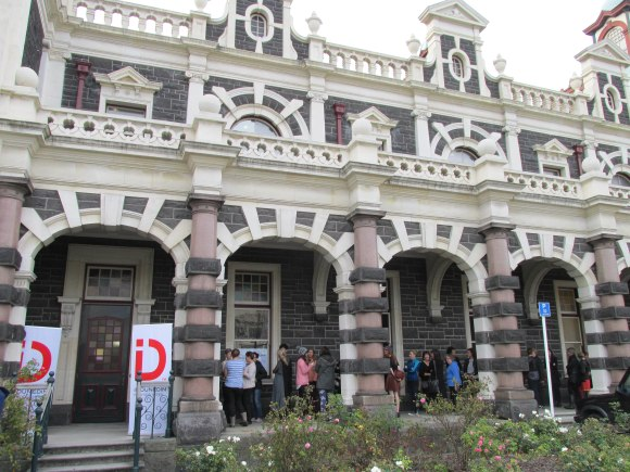 The queue forms outside the Dunedin Railway Station.